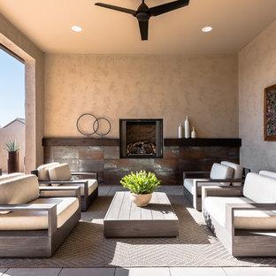 Esempio di un patio o portico american style di medie dimensioni con pavimentazioni in cemento e un tetto a sbalzo