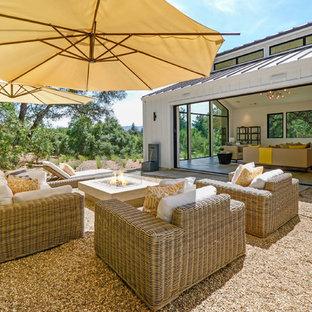 Immagine di un patio o portico country nel cortile laterale con un focolare, ghiaia e nessuna copertura