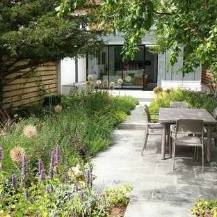 This is an example of a contemporary back patio in Oxfordshire with no cover.
