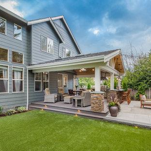 Esempio di un grande patio o portico stile americano dietro casa con pedane e un tetto a sbalzo