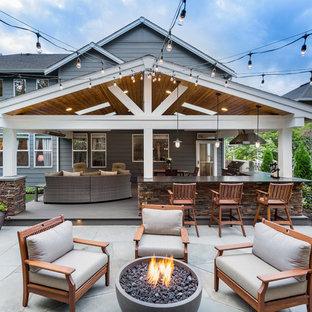 Imagen de patio clásico renovado, grande, sin cubierta, en patio trasero, con brasero y losas de hormigón