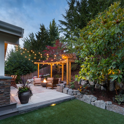 Inspiration for a large transitional backyard concrete paver patio remodel in Seattle with a fire pit
