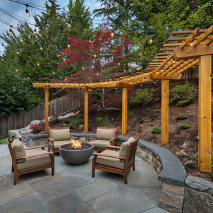 Patio - large transitional backyard stone patio idea in Seattle with a fire pit and a pergola