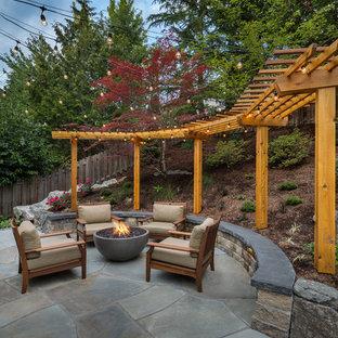Imagen de patio clásico renovado, grande, en patio trasero, con brasero, adoquines de piedra natural y pérgola