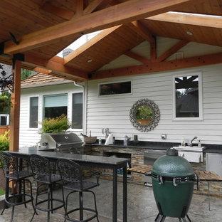 Esempio di un patio o portico boho chic di medie dimensioni e dietro casa con cemento stampato e un tetto a sbalzo