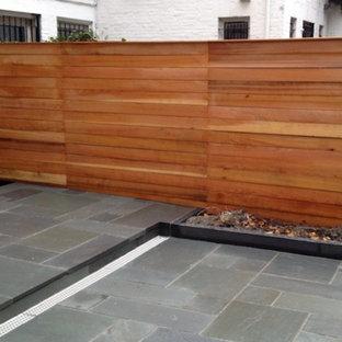 Idee per un piccolo patio o portico tradizionale dietro casa con piastrelle e un tetto a sbalzo