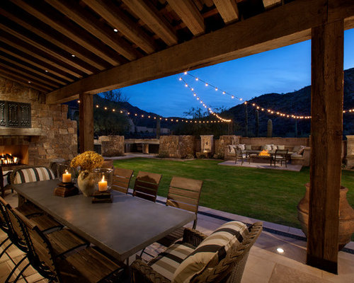 Example of a tuscan backyard patio design in Phoenix with a fire pit