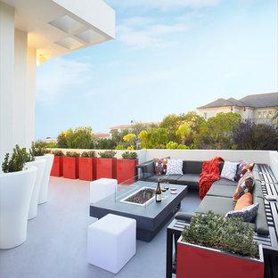 Idee per un patio o portico tropicale di medie dimensioni e dietro casa con un focolare, lastre di cemento e nessuna copertura