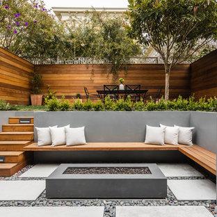 Modelo de patio moderno, sin cubierta, en patio trasero, con brasero y adoquines de hormigón