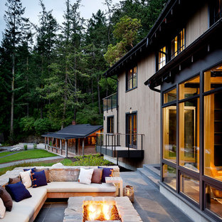 Example of a large mountain style backyard deck design in Seattle with a fire pit and no cover