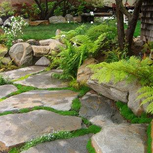 Example of a small asian backyard stone patio fountain design in San Luis Obispo with no cover