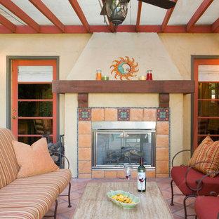 Aménagement d'une terrasse méditerranéenne de taille moyenne avec un foyer extérieur, une pergola et du carrelage.