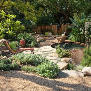 Esempio di un patio o portico rustico dietro casa con un focolare e pavimentazioni in pietra naturale