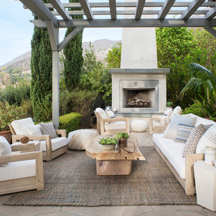 Example of a mid-sized coastal backyard stone patio design in Santa Barbara with a pergola and a fireplace