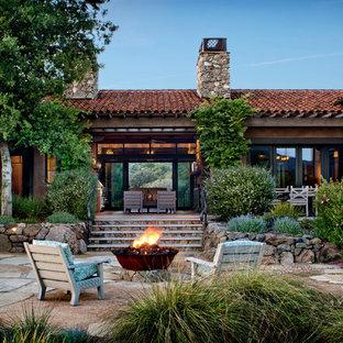 Пример оригинального дизайна: большой дворик на заднем дворе с местом для костра и покрытием из каменной брусчатки без защиты от солнца
