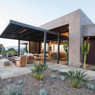 Idee per un grande patio o portico stile americano dietro casa con un focolare, pavimentazioni in pietra naturale e un tetto a sbalzo