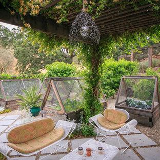 Diseño de patio rústico con adoquines de hormigón, pérgola y huerto