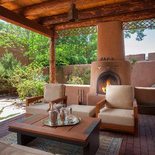 Réalisation d'une terrasse sud-ouest américain avec un foyer extérieur, des pavés en brique et une pergola.