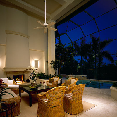 Elegant patio photo in Miami with a fire pit and a roof extension