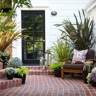 Cette photo montre une terrasse chic avec des pavés en brique.