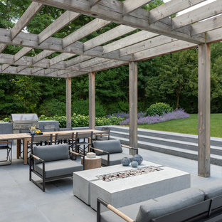 Inspiration for a country back patio in New York with an outdoor kitchen and a pergola.