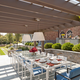 Example of a coastal patio design in New York with a pergola