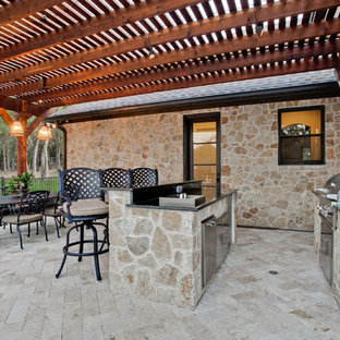 This is an example of a large mediterranean patio in Dallas with an outdoor kitchen, a pergola and brick paving.
