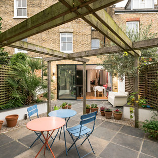 Inspiration for a medium sized classic back patio in London with a living wall and a pergola.