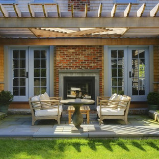 Design ideas for a transitional patio in Boston with a fire feature and a pergola.
