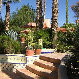 Foto di un ampio patio o portico stile americano dietro casa con pavimentazioni in pietra naturale e una pergola