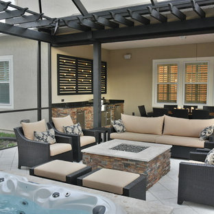 Patio kitchen - mid-sized tropical backyard tile patio kitchen idea in Jacksonville with a pergola