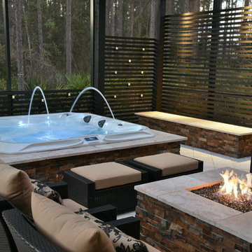 Screened area with sunken spa, fire pit and outdoor kitchen.
