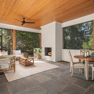 Esempio di un grande patio o portico classico dietro casa con un caminetto, pavimentazioni in pietra naturale e un tetto a sbalzo