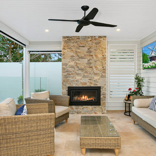Inspiration for a beach style backyard patio in Melbourne with with fireplace and a roof extension.