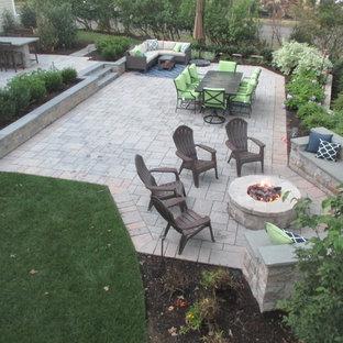 Immagine di un grande patio o portico tradizionale dietro casa con un focolare, pavimentazioni in pietra naturale e nessuna copertura
