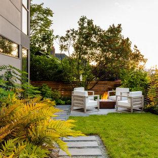 Foto di un piccolo patio o portico contemporaneo dietro casa con un focolare, pavimentazioni in cemento e nessuna copertura