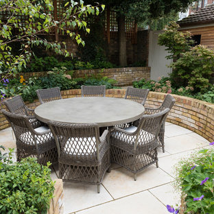 Design ideas for a medium sized traditional back patio in London with natural stone paving and no cover.