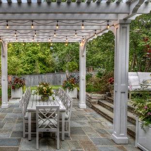 Imagen de patio clásico con adoquines de piedra natural y pérgola