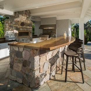 Esempio di un grande patio o portico tradizionale dietro casa con pavimentazioni in pietra naturale e una pergola