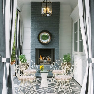 This is an example of a shabby-chic style patio in New York with a roof extension and with fireplace.