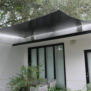 This is an example of a medium sized modern back patio in Miami with an awning.