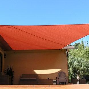Immagine di un piccolo patio o portico costiero dietro casa con lastre di cemento e un parasole