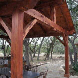 Example of a large arts and crafts backyard stone patio kitchen design in Austin with a gazebo