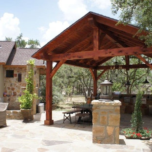 Inspiration for a large craftsman backyard stone patio kitchen remodel in Austin with a gazebo