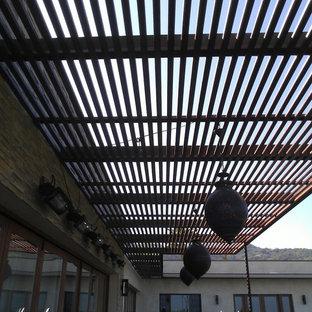 Esempio di un grande patio o portico minimalista dietro casa con cemento stampato e un parasole