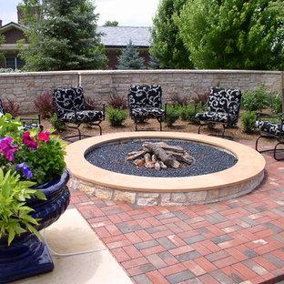 Ispirazione per un patio o portico tradizionale con pavimentazioni in mattoni e un focolare