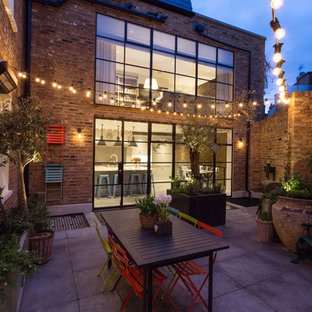 Design ideas for a medium sized traditional back patio in London with a potted garden, concrete paving and no cover.