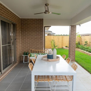 Photo of a mid-sized beach style backyard patio in Brisbane with tile and a roof extension.