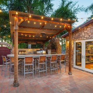 Idée de décoration pour une terrasse avec une cuisine extérieure arrière ethnique de taille moyenne avec du carrelage et un gazebo ou pavillon.