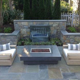 Ispirazione per un patio o portico contemporaneo dietro casa e di medie dimensioni con fontane, pavimentazioni in pietra naturale e nessuna copertura